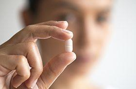 Patient holding white sedative pill