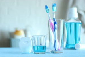 Dental hygiene tools: floss, mouthwash, and two toothbrushes