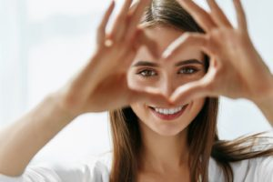 woman with healthy smile making heart shape with hands