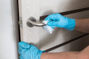 disinfecting door handle as part of dental safety protocol